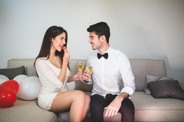 Mujer elegante comiendo una fresa mientras brinda con su novio Foto gratis