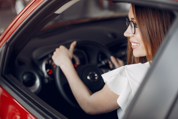 Mujer elegante y elegante en un salón de autos. Foto gratis