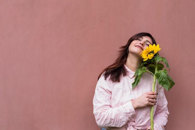 Mujer elegante con girasol en manos soñando alegremente Foto gratis