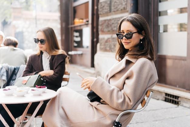 Mujer elegante joven que presenta en café moderno de la calle. Foto gratis