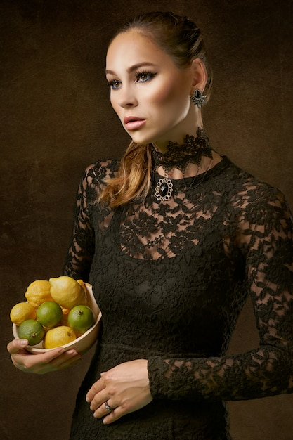 Mujer elegante con limones y limas Foto gratis