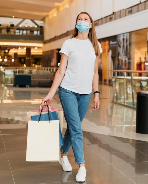 Mujer elegante, proceso de llevar, bolsas de compras Foto gratis