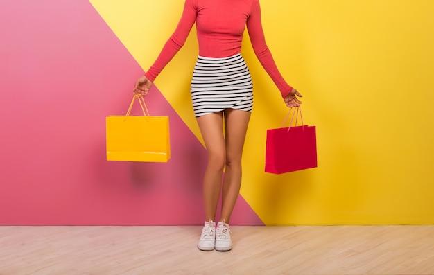 Mujer en elegante traje colorido con bolsas de compras en las manos Foto gratis