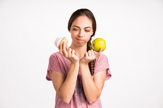 Mujer elegir cupcake sobre apple Foto gratis