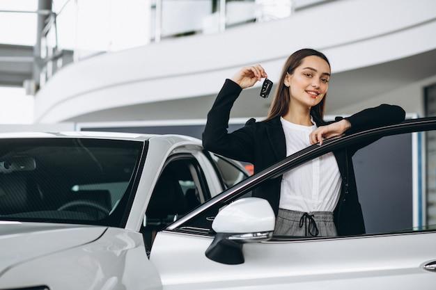 Mujer eligiendo un automóvil en una sala de exposición de automóviles Foto gratis