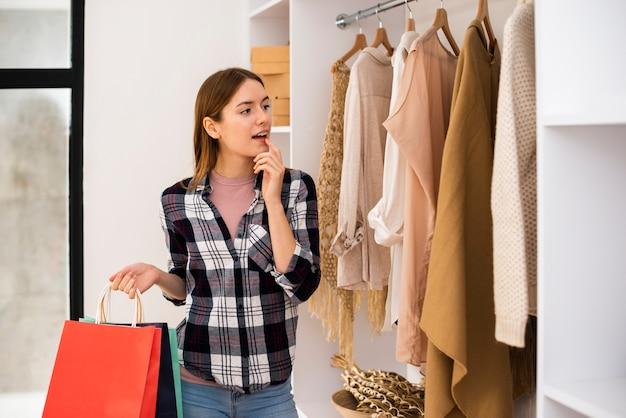 Mujer eligiendo ropa para un armario Foto gratis