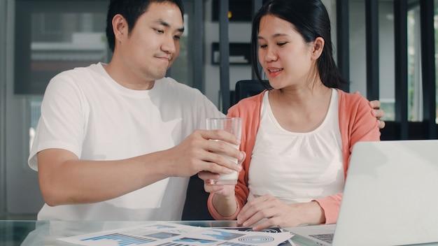 Mujer embarazada asiática joven que usa registros del ordenador portátil de ingresos y gastos en el hogar. papá le daba leche a su esposa mientras trabajaba en la sala de estar de la casa por la mañana con un presupuesto récord, impuestos y documentos financieros. Foto gratis