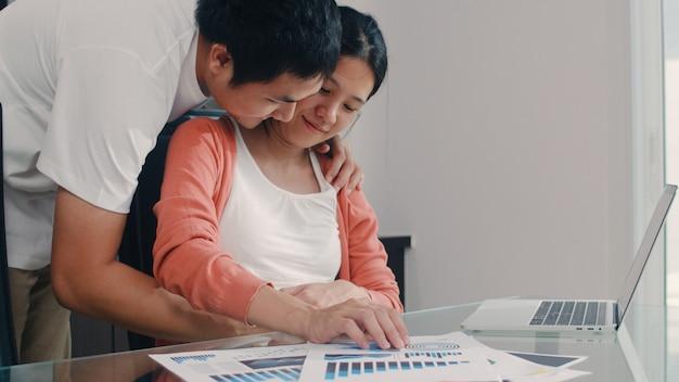 Mujer embarazada asiática joven que usa registros del ordenador portátil de ingresos y gastos en el hogar. papá le toca el vientre a su esposa mientras trabajaba en la sala de estar de su casa con un presupuesto récord, impuestos, documentos financieros Foto gratis