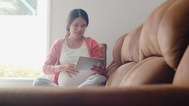 La mujer embarazada asiática joven que usa la tableta busca la información del embarazo. mamá se siente feliz sonriendo positiva y pacífica mientras cuida a su hijo acostado en el sofá en la sala de estar en casa. Foto gratis