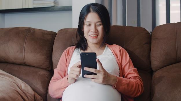 La mujer embarazada asiática joven que usa el teléfono móvil busca la información del embarazo. mamá se siente feliz sonriendo positiva y pacífica mientras cuida a su hijo acostado en el sofá en la sala de estar en casa. Foto gratis
