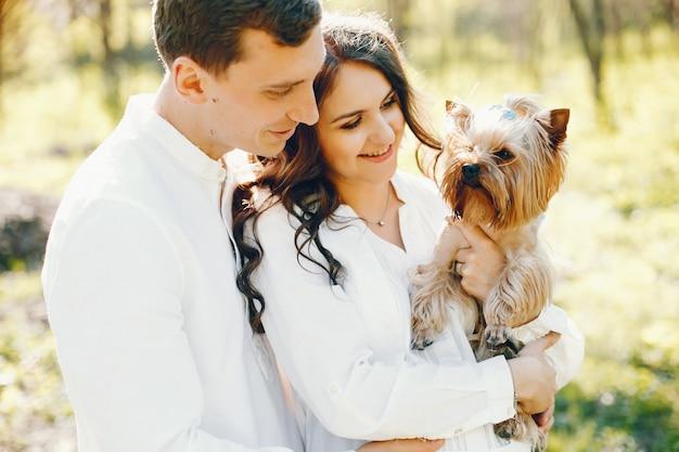 Mujer embarazada brillante y feliz caminando en el parque con su marido y perro Foto gratis