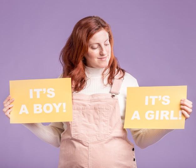 Mujer embarazada busca papel con género de bebé Foto gratis