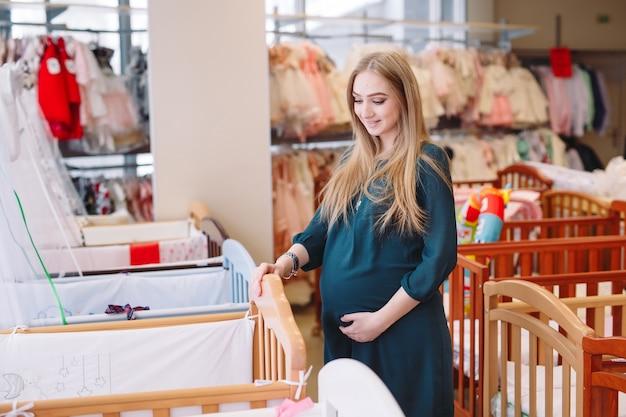 La mujer embarazada elige una cuna en la tienda. Foto Premium