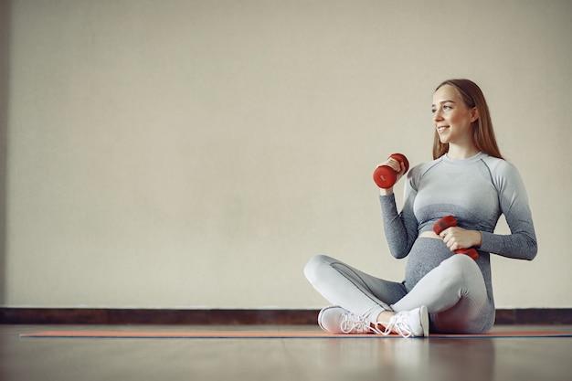 Mujer embarazada entrenando en un gimnasio Foto gratis