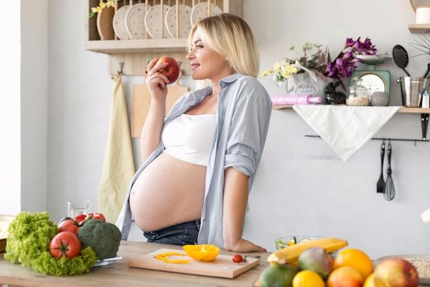 Mujer embarazada de lado que come una manzana Foto gratis