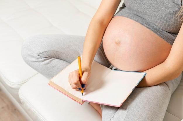 Mujer embarazada manos escribiendo algo en un libro Foto gratis