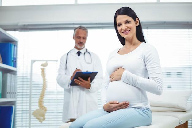Mujer embarazada con médico en clínica Foto Premium