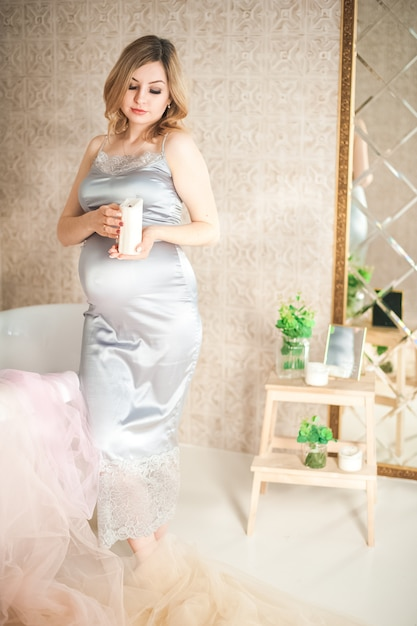 Mujer embarazada en el primer plano del baño. embarazada cerca del baño en un espacio gris de bata y copia. Foto Premium