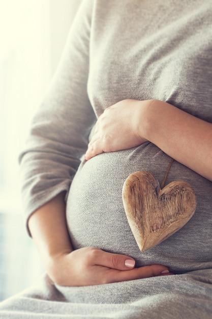 Mujer embarazada sujetando un corazón mientras se toca la barriga Foto gratis