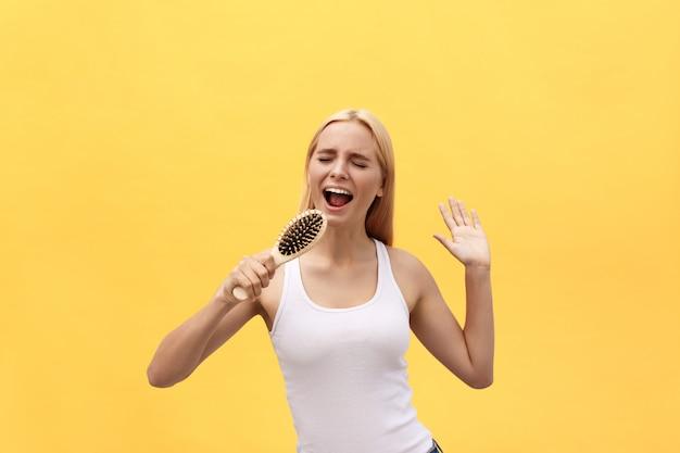 Mujer emocional joven que canta con el peine mientras que viste. aislado sobre fondo amarillo. Foto Premium