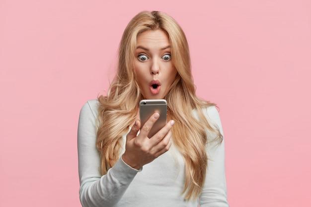 Mujer emprendedora o empresaria decepcionada con las noticias de su colega, lee el mensaje en el teléfono inteligente, sorprendida de recibir la responsabilidad de preparar un proyecto difícil para la reunión de mañana Foto gratis