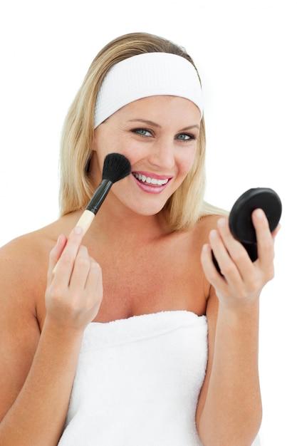 Mujer encantada poniéndose maquillaje Foto Premium