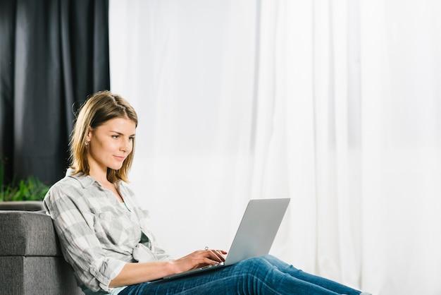 Mujer encantadora que usa la computadora portátil cerca del sofá Foto gratis