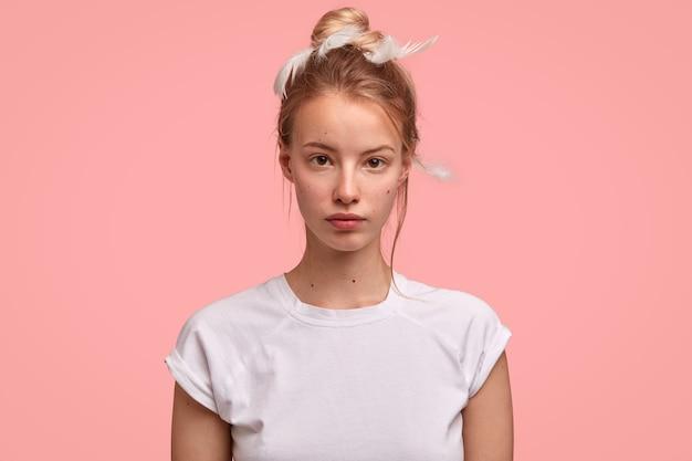 Una mujer encantadora seria mira directamente a la cámara, tiene una expresión soñolienta, usa una camiseta informal y plumas Foto gratis