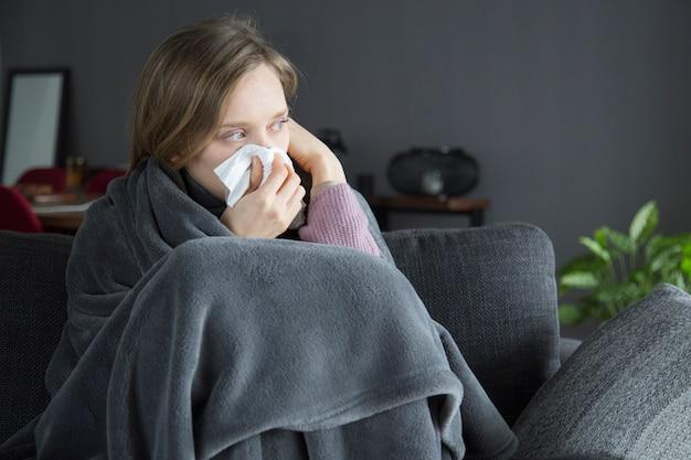 Mujer enferma aburrida que lleva a cabo la mano en la cabeza, soplando la nariz con la servilleta Foto gratis