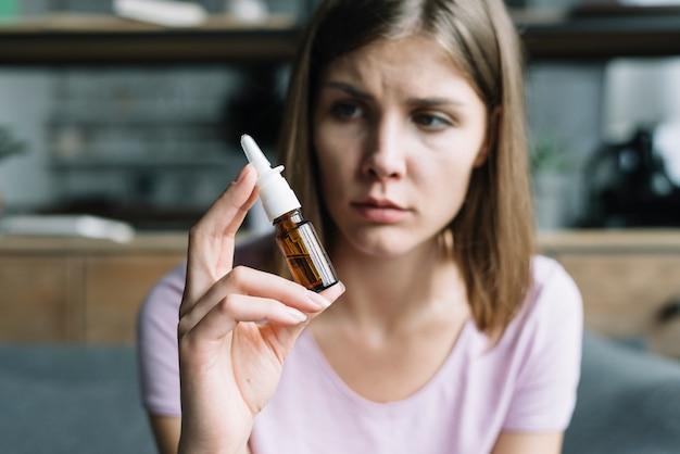 Mujer enferma con aerosol nasal en la mano Foto gratis