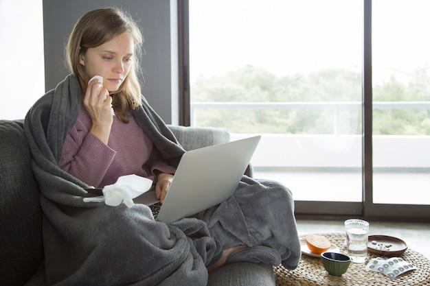 Mujer enferma tomando una servilleta en la cara, sosteniendo una computadora portátil en las rodillas Foto gratis
