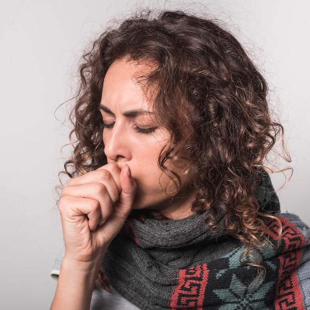 Mujer enferma tos sobre fondo gris Foto gratis
