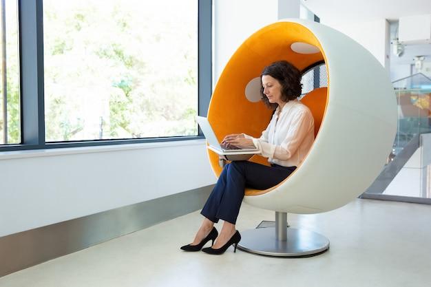 Mujer enfocada usando laptop mientras está sentado en una silla esférica Foto gratis