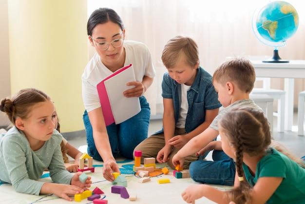 Mujer enseñando a los niños un nuevo juego en el jardín de infantes Foto Premium
