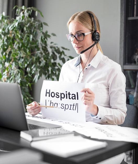 Mujer enseñando a sus alumnos la definición de hospital en línea Foto gratis