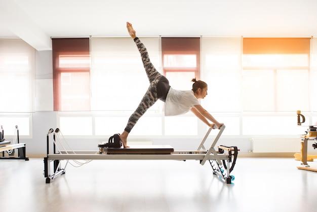 Mujer entrenando ejercicios de pilates en gimnasio cubierto Foto Premium