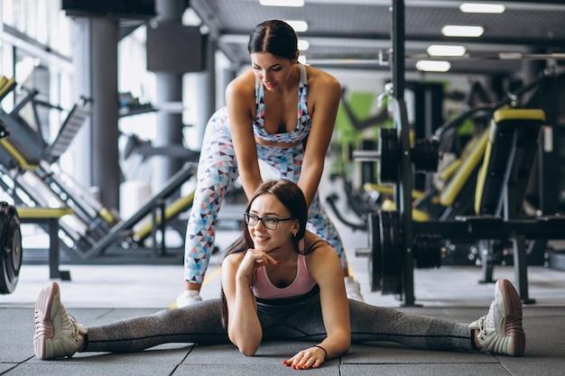 Mujer entrenando en el gimnasio con entrenador de fitness femenino Foto gratis