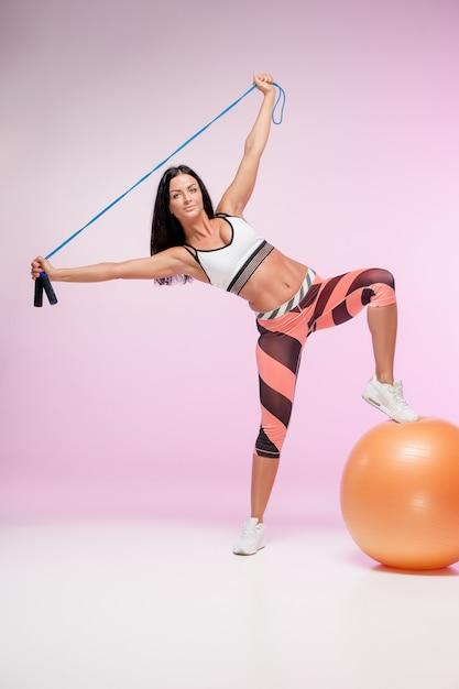 Mujer entrenando en ropa deportiva con saltar la cuerda Foto gratis