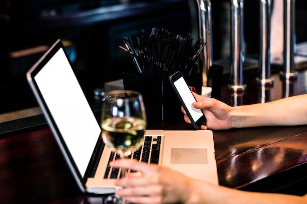 Mujer enviando mensajes de texto y usando una computadora ...