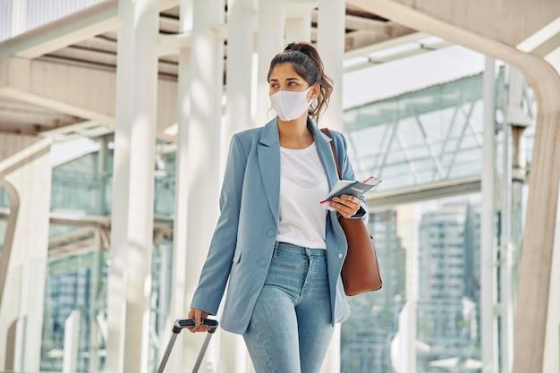Mujer con equipaje y máscara médica en el aeropuerto durante la pandemia Foto gratis