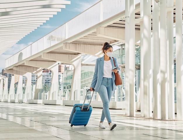 Mujer con equipaje durante la pandemia en el aeropuerto Foto gratis