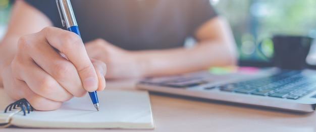 Mujer escribiendo en un bloc de notas con un bolígrafo en la oficina Foto Premium