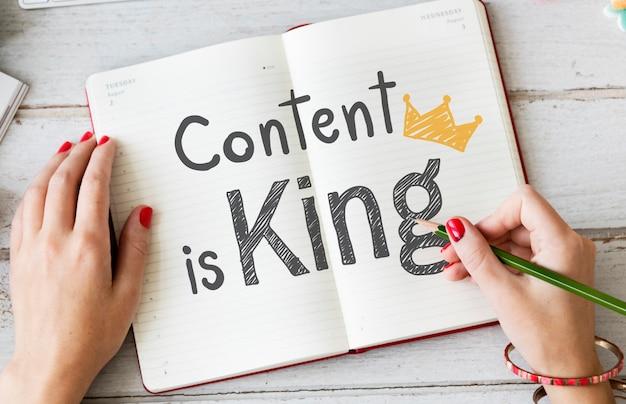 Mujer escribiendo contenido es rey en un cuaderno Foto Premium