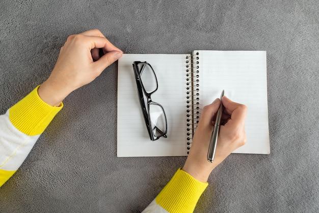 La mujer está escribiendo en el cuaderno. Foto Premium