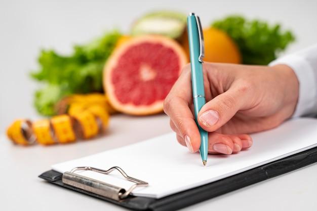 Mujer escribiendo y fruta borrosa Foto gratis