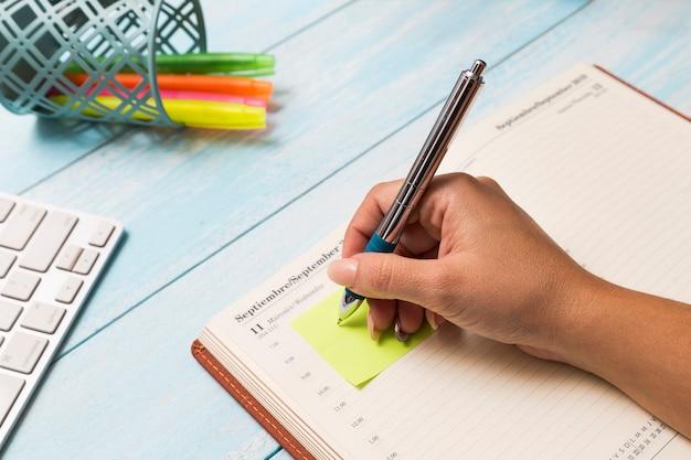 Mujer escribiendo nota en diario Foto gratis