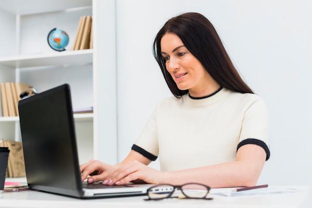 Mujer escribiendo en el teclado del ordenador portátil en la oficina Foto gratis