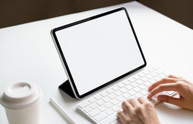 Mujer escribiendo teclado portátil y tableta pantalla en blanco en la mesa imitan para promover sus productos. concepto de futuro y tendencia a internet para facilitar el acceso a la información. Foto Premium