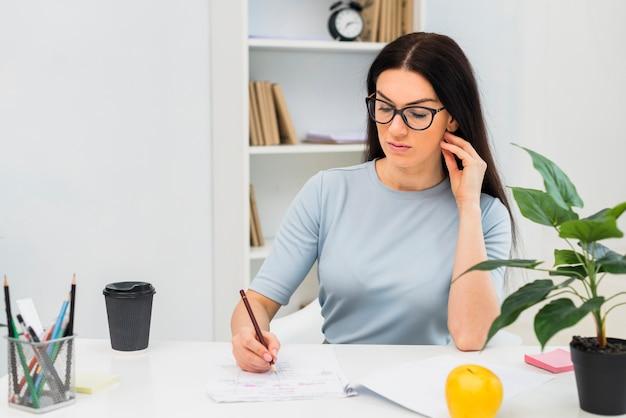 Mujer, escritura, en, papeles, en la mesa Foto gratis