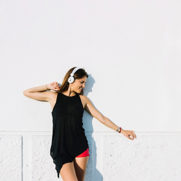 Mujer escuchando música en auriculares frente a la pared Foto gratis